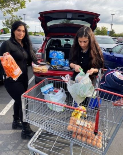 Two female students loading groceries from a cart into their car